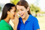 teenage girl Sharing Secret With Friend In Park